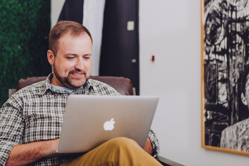 a bearded white man using a laptop