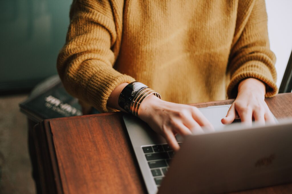 white woman in a yellow jumper typing on a laptop