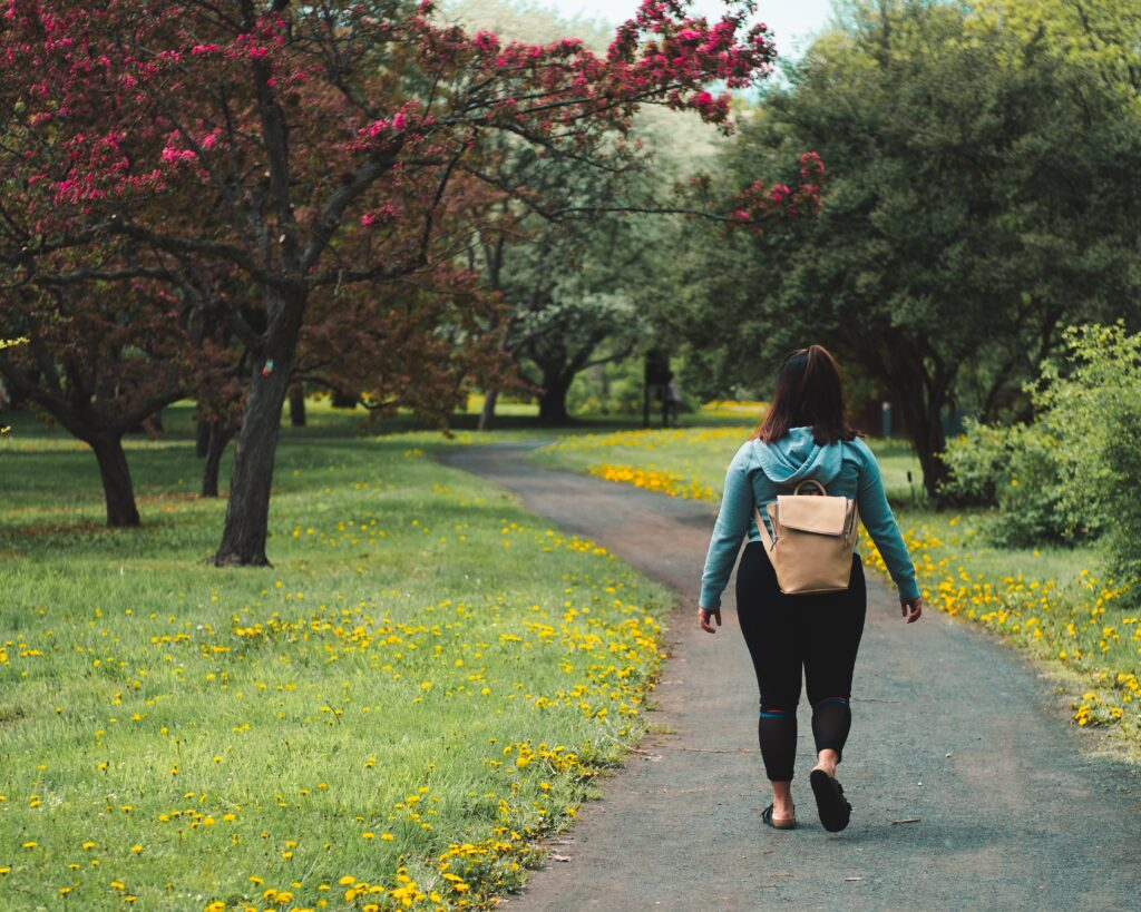 A young dark haired woman walking along a path through a park