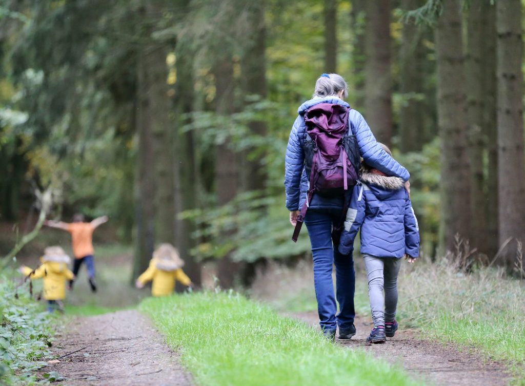 a woman walking with a child in a forest