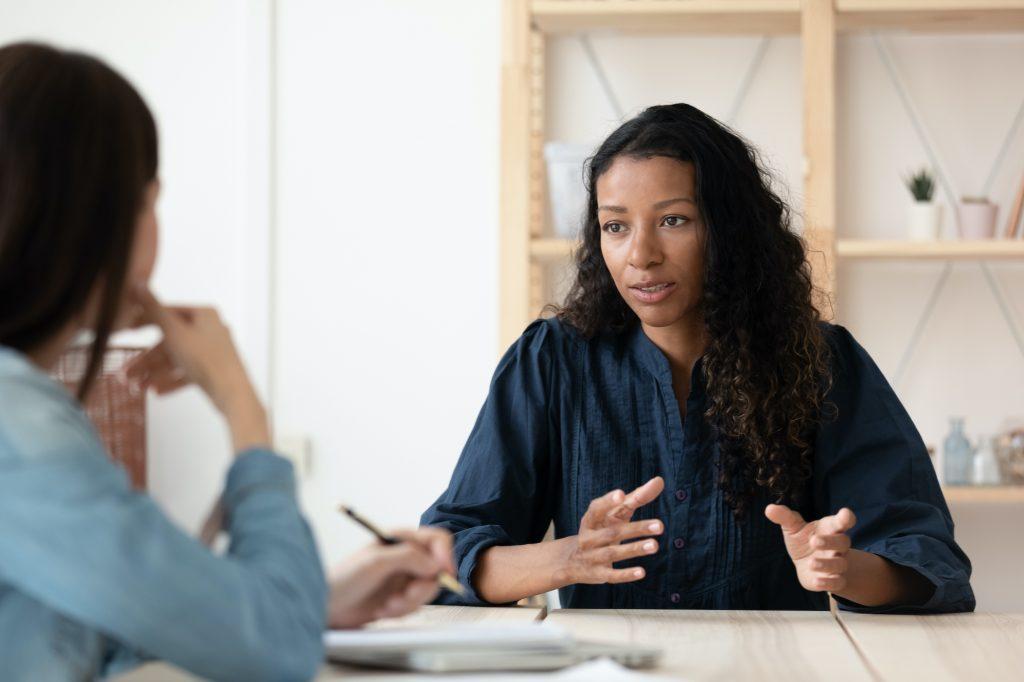 two women speaking across a desk